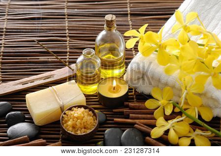 Spa setting with yellow orchid, oil, soap ,stones. Towel on mat background