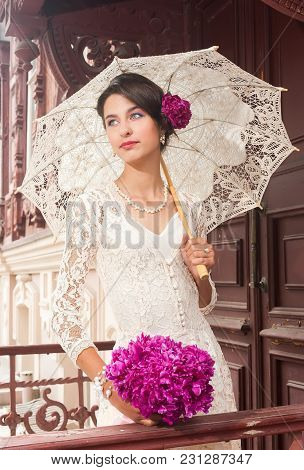 Portrait Of Young Beautiful Smiling Woman With Peony Flowers And Lacy Umbrella Over Old Wooden House