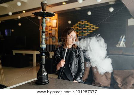 Attractive Female Relaxing In A Bar And Smokes A Hookah