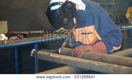 Industrial Worker At The Factory Welding Close Up. Electric Wheel Grinding On Steel Structure In Fac