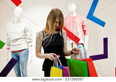 Girl With Shopping Bags In The Mall Against Mannequins In The Show-window.