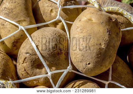 A Pile Of Potatoes Lying In A Potato Bag In The Foreground