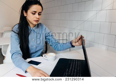 Serious Young Business Woman In Blue Shirt Working On Laptop