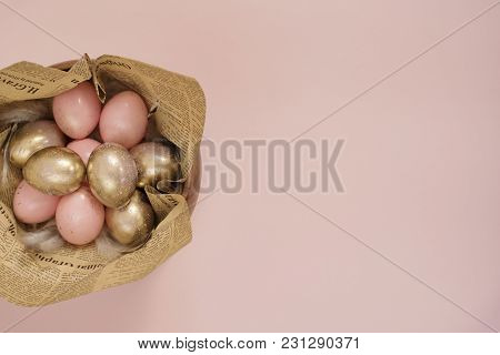 Easter Eggs In A Wood Bowl. Pink And Gold Easter Eggs. Pink Pastel Easter Concept With Eggs And Feat