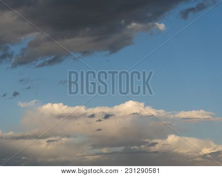 Gentle Natural Picture Of The Setting Sun: From Above A Black Cloud, From Below White Stripes Of A C
