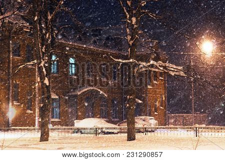 Building Of Red Brick Near The Park In Winter, Bad Weather, Wind And Snow Blizzard At Night.