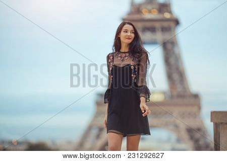 Elegant Romantic Parisian Woman In Black Sexy Dress With Flowers Walking Near The Eiffel Tower At Tr