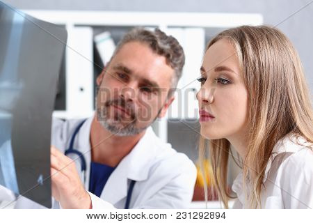 Mature Male Doctor Hold In Arm And Look At Xray Photography Discussing It With Female Patient Portra