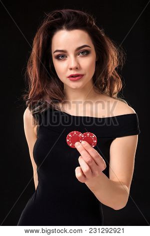 Smiling Girl Holding A Gambling Chips In Her Hands On Black Background. Sexy Brunette In A Dress. Po