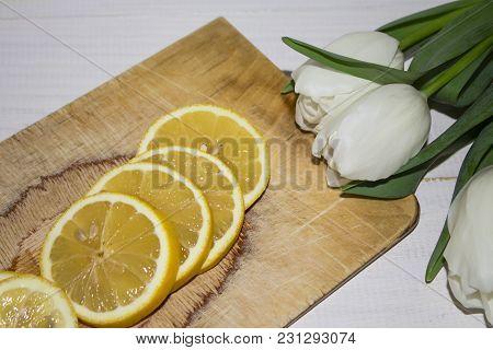 Fresh Lemons On The Brown Table. Ripe Lemons On The Wooden Background. Fresh Lemon Sliced In Lobules