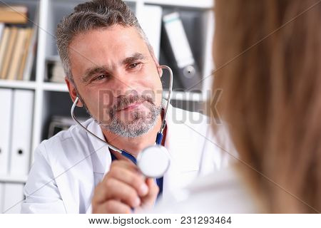 Handsome Mature Smiling Male Doctor Hold In Arm Stethoscope Head Going To Listen Patient. Tool Shop
