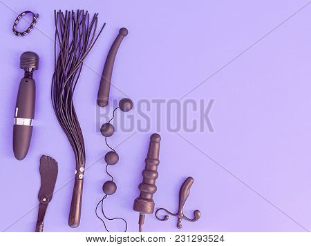 Various Sex Toys (leather Whip, Dildo, Vibrator, Love Balls And Other) Are On A Purple Background. T