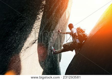 Brave Man Sitting In Canyon With Backpack, Intentional Sun Glare