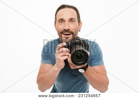 Portrait of an excited mature man dressed in t-shirt holding photo camera isolated over white background