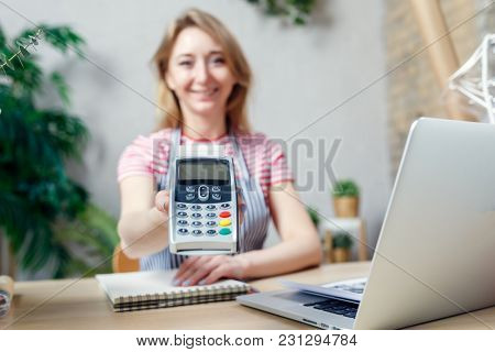 Woman is offering payment terminal for paying with credit card