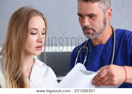 Smiling Handsome Doctor Communicate With Patient Holding Silver Pen And Showing Pad. Physical Agreem