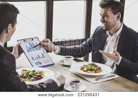 Smiling Businessmen Analyzing Graphs During A Business Lunch.