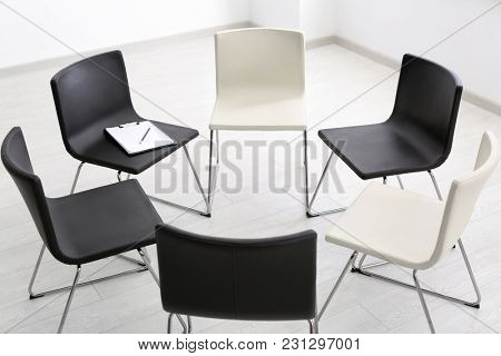 Black and white chairs in empty room for group therapy
