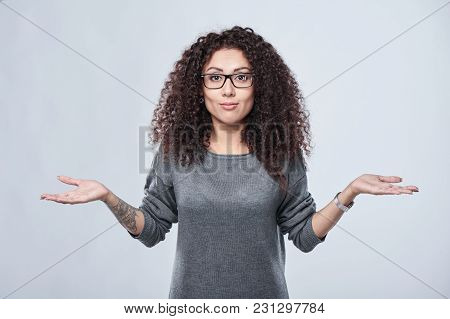 Closeup Of Amazed Curly Woman In Eyeglasses With Open Spread Hands Shrugging Shoulders, Over Grey Ba
