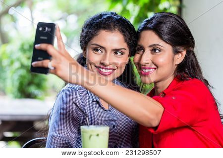Indian girls in cafe taking selfie with smart phone