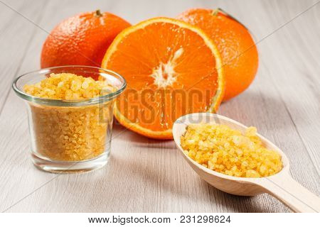 Cut Orange With Two Whole Oranges, Glass Bowl And Wooden Spoon With Yellow Sea Salt On Wooden Desk.
