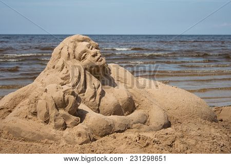 Sculpture Of A Loving Couple Of Sand On The Beach. Yellow Sand, Blue Sea. Romance, Sunny Day