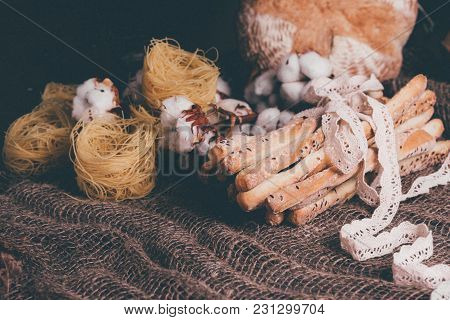 Delicious Breadsticks Grissini. Italian Appetizers. Wooden Dark Background And Burlap Flowers Of Cot