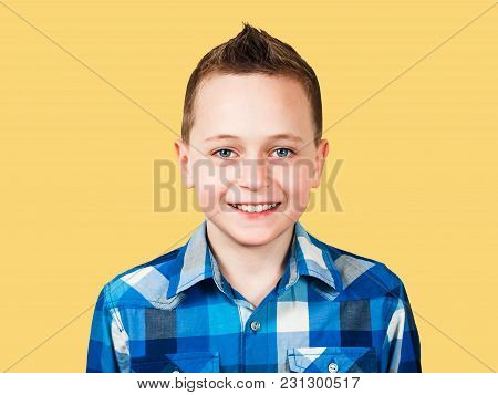 Portrait Of A Smiling Boy Dressed In Blue Shirt Looks Forward, Closeup, Isolated On White Background