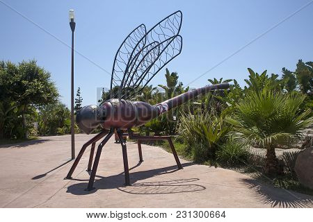Benidorm-jun 10, 2015: Entrance To Terra Natura Benidorm Zoo. A Giant Statue Of A Dragonfly At The E