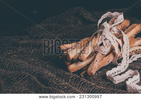 Delicious Breadsticks Grissini. Italian Appetizers. Wooden Dark Background And Burlap And Natural Li