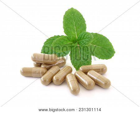 Mint Leaves And Pill Close Up On Background