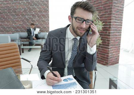 businessman talking on smart phone in modern office