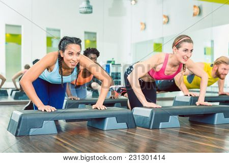 Determined young women exercising push-ups on aerobic stepper platforms during group workout class at a modern fitness club