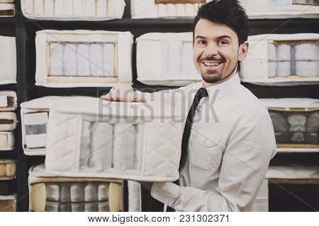 The Young Salesman Is Showing Quality Mattresses In The Store.