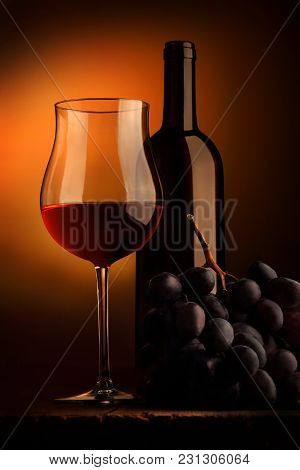 Goblet Of Red Wine With Bottle And Bunch Of Grap