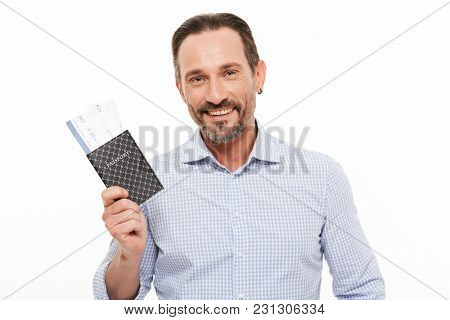 Portrait of a happy mature man dressed in shirt holding passport isolated over white background