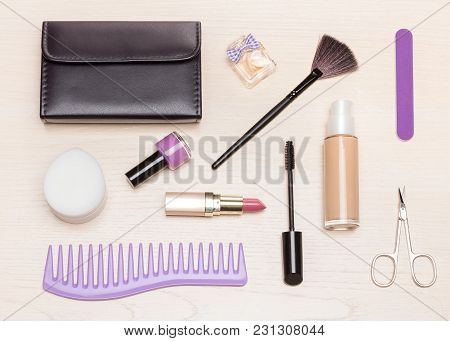 Basic Contents Of Cosmetic Bag On Light Wood Table, Flat Lay. Essential Make Up Beauty Products And