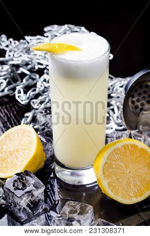 Alcoholic Cocktail - Yellow Bird Drink With Slice Lemon In A Glass With Cube Ice In Shaker On A Blac