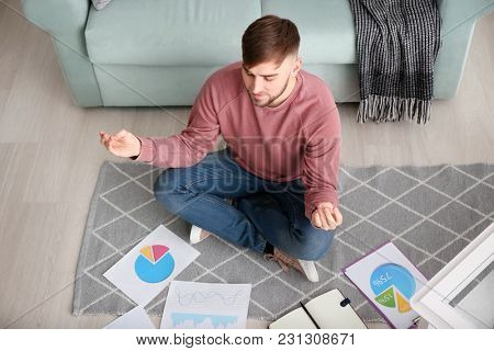 Young man relaxing in meditation posture at home