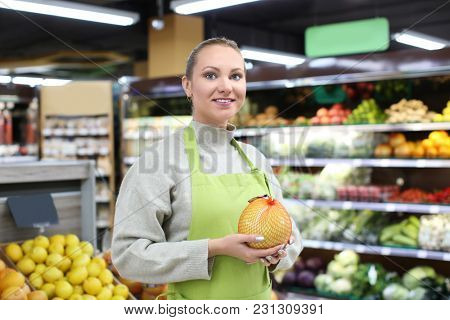 Portrait of young woman with citrus fruit in shop. Small business owner
