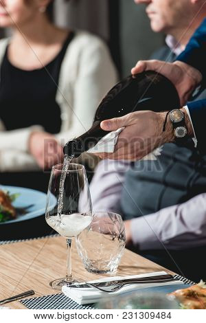 Served Table At Wine Tasting. Sommelier At Wine Tasting Pouring Champagne Into Glass
