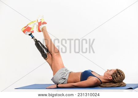 Full length portrait of a healthy young disabled sportswoman doing exercises on a sports man isolated over white background