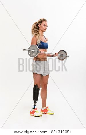 Full length portrait of a motivated young disabled sportswoman lifting heavy barbell isolated over white background