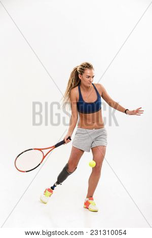Full length portrait of a motivated young disabled sportswoman with leg prosthesis doing exercises with tennis racket isolated over white background