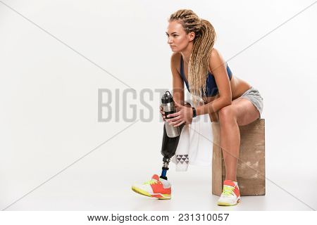 Image of young disabled sports woman with prosthesis sitting isolated over white background. Looking aside drinking water.