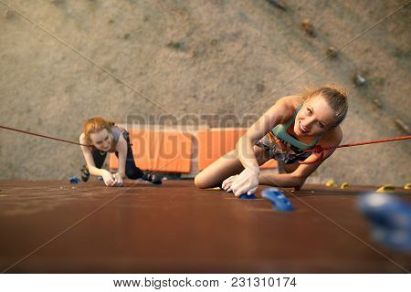 Strong Woman And Business Concept. Top View Of Two Young Climbers Approaching To Finishing Point On