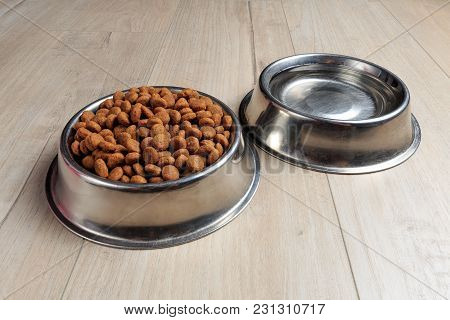 Bowls With Dog Food And Water On Wood Floor