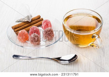 Red Marmalade, Teabag, Cinnamon Sticks In Saucer, Cup Of Tea And Teaspoon On Wooden Table