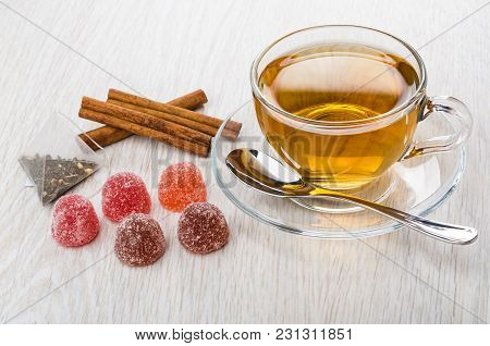 Red Marmalade, Teabag, Cinnamon Sticks, Cup Of Tea And Teaspoon On Saucer On Wooden Table