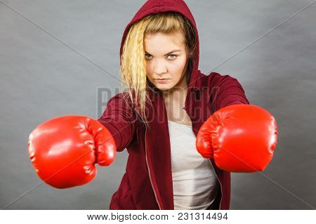 Sporty Woman Wearing Red Boxing Gloves, Fighting. Studio Shot On Dark Background.